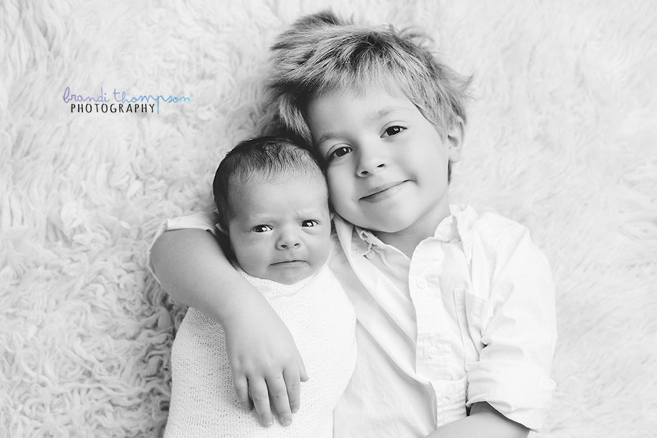 newborn photography - black and white image of newborn baby with eyes open and older brother
