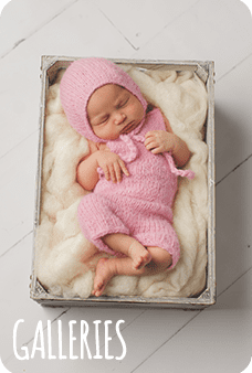 Newborn baby girl sleeping in pink outfit in box